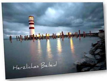 Christliche Trauerkarte: Leuchtturm vor Regenwolken
