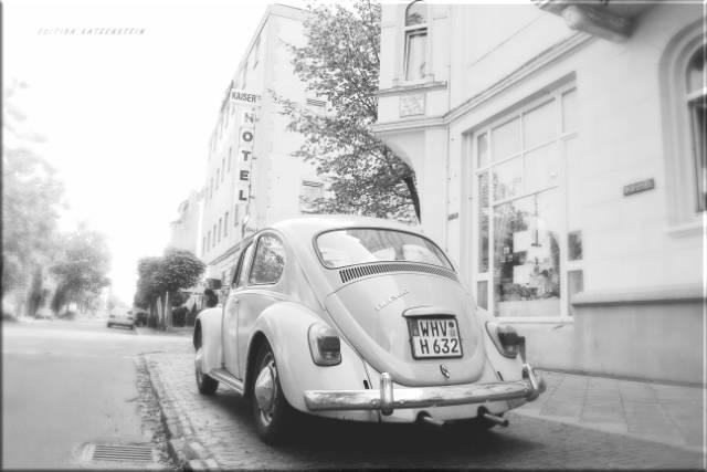 Leinwanddruck: Weißer VW Käfer auf Bürgersteig